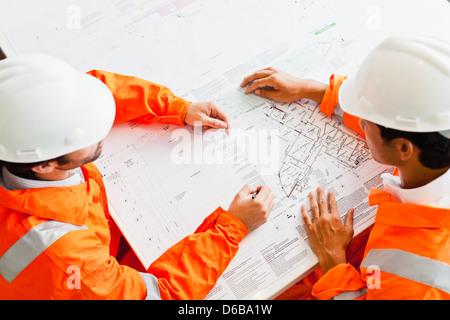 Businessmen reading blueprints - Stock Photo