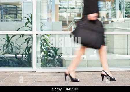 Businesswoman walking on city street - Stock Photo
