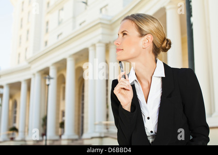 Businesswoman thinking outdoors - Stock Photo