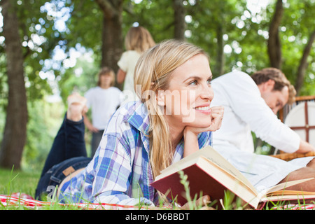 Woman reading on blanket in park - Stock Photo