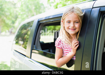 Smiling girl standing in car window - Stock Photo