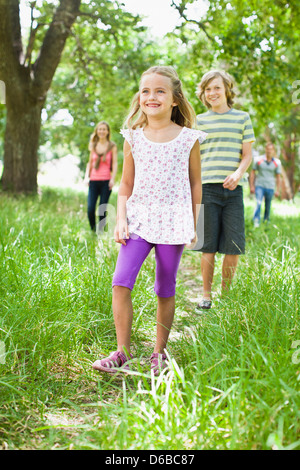 Children walking together in grass - Stock Photo
