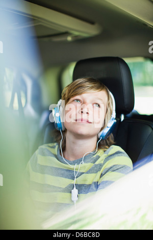 Boy listening to headphones in car - Stock Photo