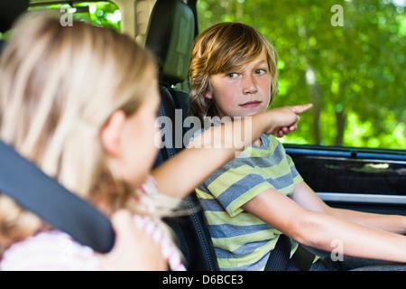 Children sitting in backseat of car - Stock Photo
