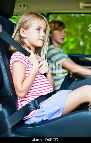 Girl sitting in car booster seat - Stock Photo