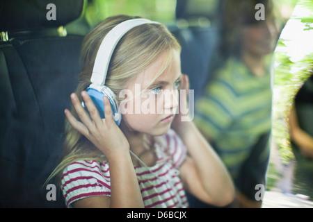 Girl listening to headphones in car - Stock Photo