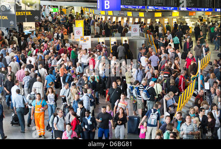 Passengers crowd in a waiting hall of the Frankfurt airport and try to reschedule their flights in Frankfurt Main, - Stock Photo
