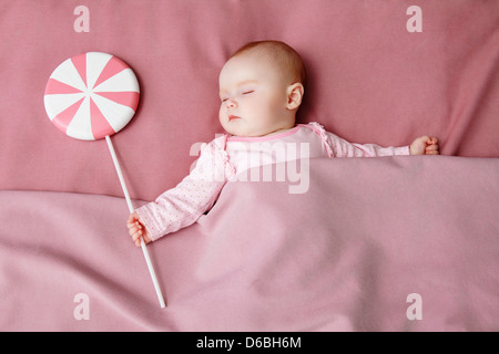 Baby girl sleeping in bed - Stock Photo