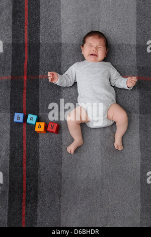 Baby boy crying on bed - Stock Photo