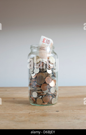 Savings jar on desk - Stock Photo
