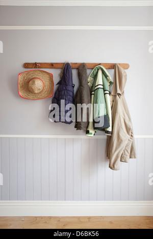 Coats and hat on coat rack - Stock Photo