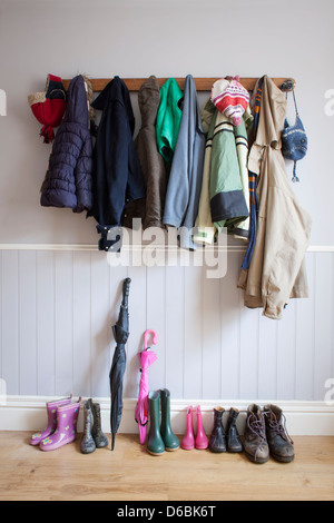 Coats on coat rack with boots - Stock Photo