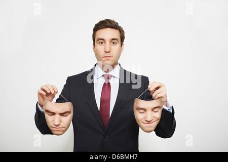 Businessman holding masks - Stock Photo