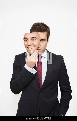 Businessman holding mask over his face - Stock Photo