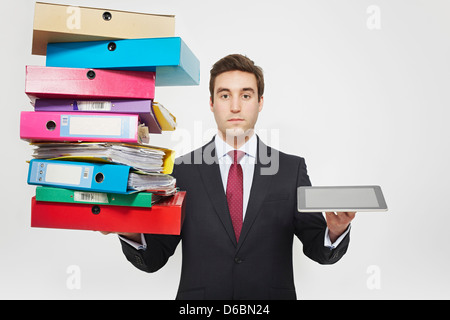 Businessman with stacks of folders and tablet computer - Stock Photo