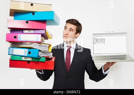 Businessman with stacks of folders and laptop - Stock Photo