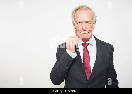 Businessman holding picture over his mouth - Stock Photo