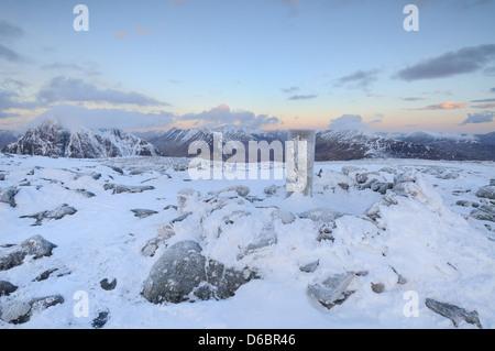 Frozen trig point on the summit of Beinn a ' Chrulaiste at dawn in winter in Glencoe, Scottish Highlands - Stock Photo