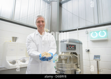 Worker with handful of oats in factory - Stock Photo