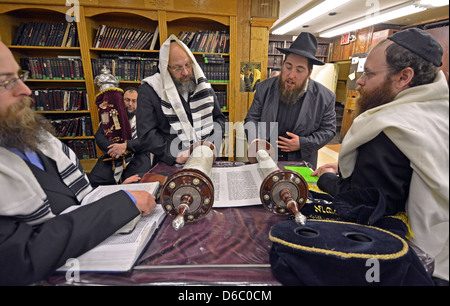 Reading from a Torah scroll at morning services during Passover at Lubavitch headquarters in Brooklyn, New York. - Stock Photo