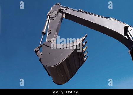 Shovel bucket against blue sky - Stock Photo