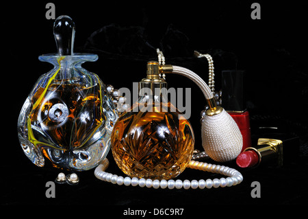 Perfume atomiser bottle, Perfume bottle with stopper and jewellery against a black background. - Stock Photo