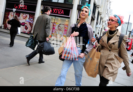 London, England, UK. Two young women in colourful clothing, shopping in Oxford Street. - Stock Photo