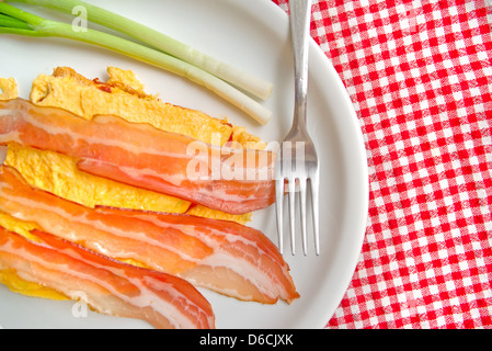 Bacon and scrambled eggs with green leek on white plate served as breakfast. Traditional breakfast with lots of - Stock Photo