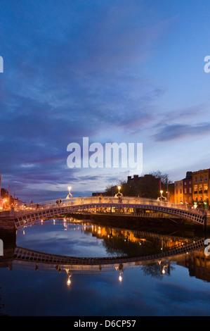 Vertical view of the Ha'Penny Bridge aka Droichead na Leathphingine or Liffey bridge in Dublin at sunset. - Stock Photo