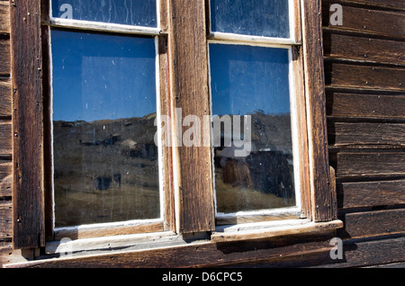 Gold mining ghost town buildings reflected in weathered window glass,  California, Bodie State Park, - Stock Photo