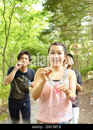 Girl and two guys blowing bubbles on a country road - Stock Photo