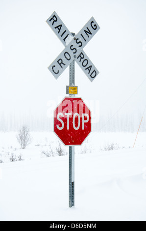 Snow covered railroad crossing in anchorage Alaska - Stock Photo