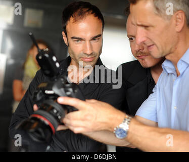 dpa-exclusive - Designers Ivan Strano (l) and Klaus Unrath (m) look at the photos of photographer Jens van Zoest - Stock Photo