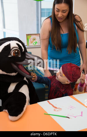 Long Beach, CA. April 16, 2013.    3-year-old Miguel Ochoa touches the beak of Marie the penguin from the Aquarium of the Pacific at Miller Children's Hospital while Miguel's mother Sandra Ochoa looks on. The Aquarium of the Pacific interactive program lets the patients at Miller Children's Hospital in Long Beach interact with costumed characters in person and experience visiting sea creatures and participate in live ocean learning with staff at the Aquarium's videoconferencing studio. Credit: Kayte Deioma/Alamy Live News
