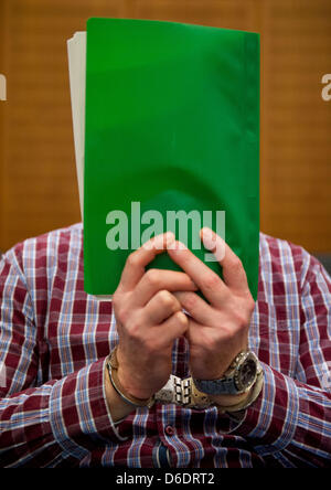 Bus hijacker Thomas Feldmann hides his face behind files at the start of his trial in a high-security court room - Stock Photo