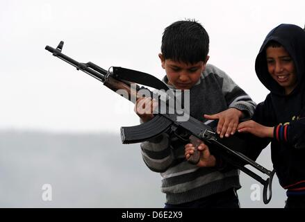 DARKOUSH, SYRIA: Syrian kids holding an assault rifle on April 16, 2013, in Darkoush, Syria. A team of 45 medical - Stock Photo