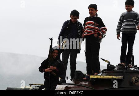 DARKOUSH, SYRIA: Syrian kids holding an assault rifle while standing on top of a tanker on April 16, 2013, in Darkoush, - Stock Photo
