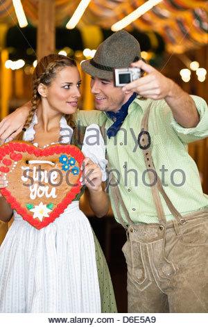 Young couple taking self portrait Oktoberfest Munich Germany - Stock Photo