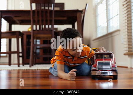 Mixed race boy playing with fire truck on floor - Stock Photo