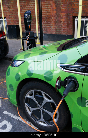 A Vauxhall Ampera zipcar plugged-in to a charging point and recharging in Camden. - Stock Photo
