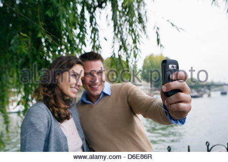 Young couple by river Seine man taking picture with camera phone Paris France - Stock Photo