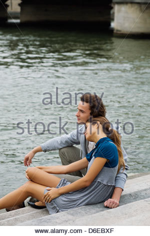 Young couple sitting steps by river Seine Paris France - Stock Photo