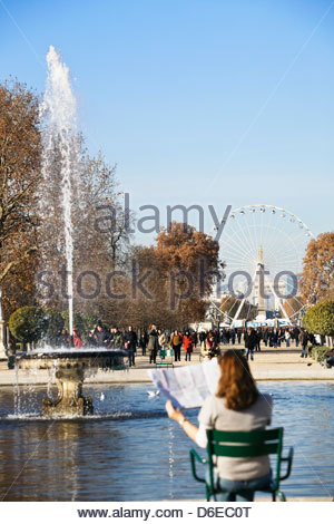 Woman looking map with Place de la Concorde big wheel in background Paris - Stock Photo