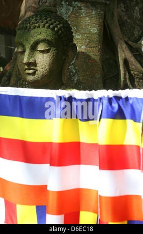 Statue with Buddhist flag, Gangaramaya Buddhist Temple, Colombo, Sri Lanka - Stock Photo