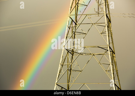 A rainbow over pylons leaving Wylfa nuclear power station on Anglesey, Wales, UK. - Stock Photo