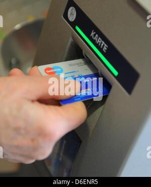 Eine Frau führt am Dienstag (07.02.2012) in München (Oberbayern) an einem Geldautomaten ihre EC-Karte in den Schlitz - Stock Photo