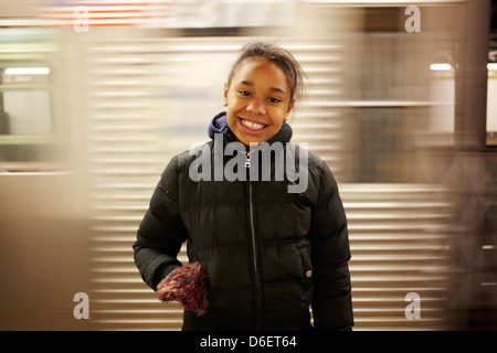 Mixed race girl smiling in subway station - Stock Photo