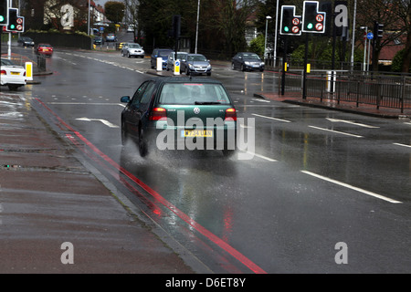 Volkswagon Golf At Traffic Lights On Crossroads in the Rain a217 Surrey England - Stock Photo
