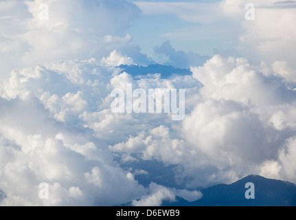 The jagged peaks of the summit of distant Gunung Kinabalu pushing through cloud Sabah Borneo - Stock Photo