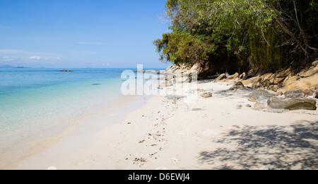 Deserted tropical beach and blue sea on the little island of Mamutik off Kota Kinabalu Malaysian Borneo - Stock Photo